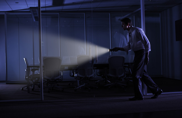 Man with flashlight in dark office