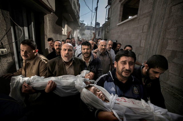 Mourners carry the bodies of a brother and sister